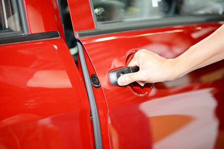 opens: Man opens the door to a new red car