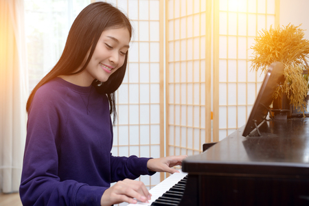 Lovely teen playing piano in the music room.