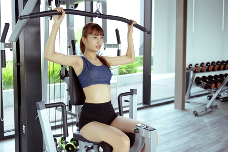 Exercise in the gym, women want to have a beautiful body with fitness. Stock Photo