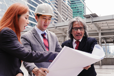 Executives, enjineer and secretaries are discussing and viewing the plan at the construction site. Stock fotó