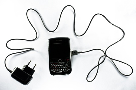 Mobile phone with charger on white background photo