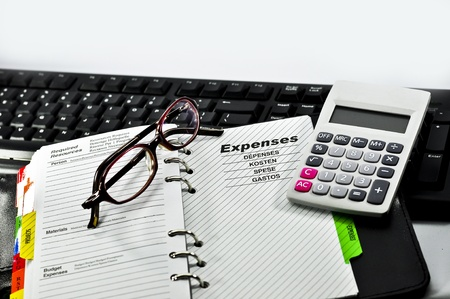 Expenses Notebook,glasses,calculator and Keyboard with white background. Stock Photo