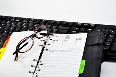 administracion de empresas: nota del proyecto, vasos y teclado con fondo blanco
