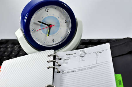 project note book,keyboard and clock with black background Stock Photo