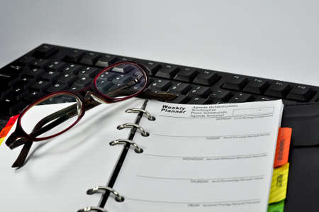 Weekly Planner Note,keyboar,glasses and clock with white background Stock Photo