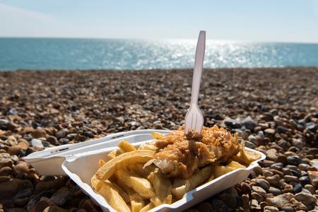 pescado frito: Pescado y patatas fritas delicioso quitan comida disfrutar en la playa