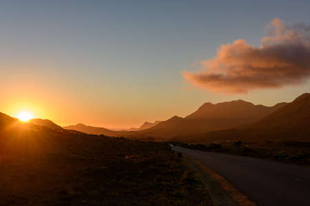 Road in Cape Peninsula national park during sunset. Cape Town, South Africa Stock Photo
