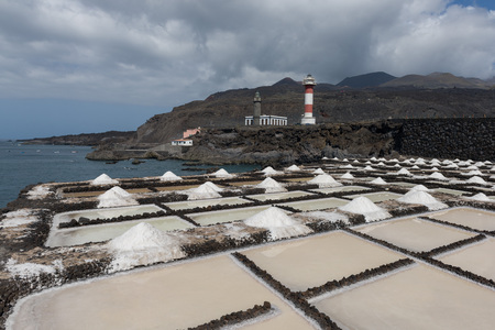 Volcanic pools on the salt manufacturing Fuencaliente with lighthouse and mountains on the background on La Palma island in Spain Stock Photo