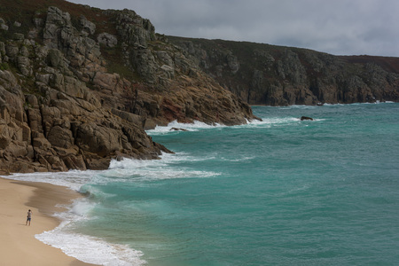 Beach in Cornwall during the day with typical British weather