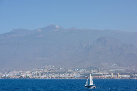View of El Teide, Los Cristianos and sailing boat from the ferry Stock Photo