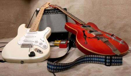 the red and cream electric guitars lay on the amplifier Stock Photo - 3289006