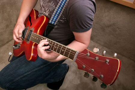 hand of guitarist playing at red electric guitar photo