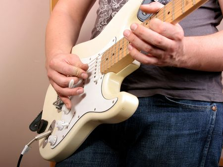 hand of guitarist playing at white electric guitar photo
