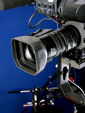 camcorder DV stand sul cinema gru con mano il controllo remoto, con sfondo blu Archivio Fotografico