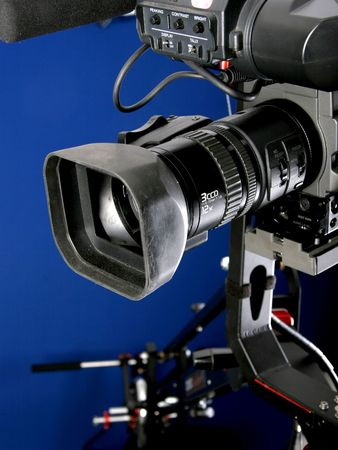 film making: dv camcorder stand on cinema crane with handly remote control with deep blue background Stock Photo