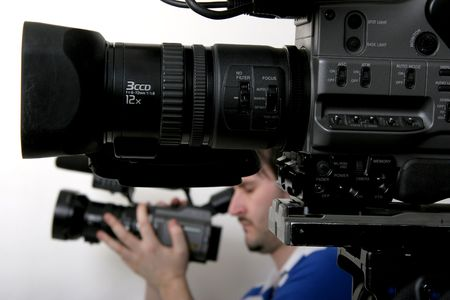 black dv camcorder stay with unfocused working cameraman on background