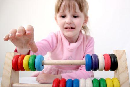 abacus: mała dziewczynka dokonać pewnych obliczeń z kolorowych drewnianych zabawek Abacus Zdjęcie Seryjne