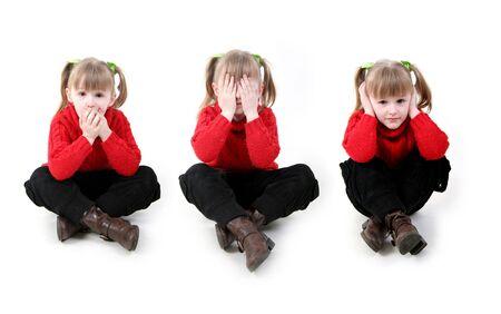 bambina in rosso cardigan sedersi in tre posizione simbolyzide antica saggezza 'non sentire il male, non vedono il male, non parlare male'  Archivio Fotografico