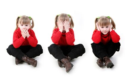 little girl in red cardigan sit down in three position simbolyzide ancient wisdom hear no evil, see no evil, speak no evil Stock Photo