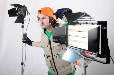 human photography: the light operator work with two luminariers in cinema processing