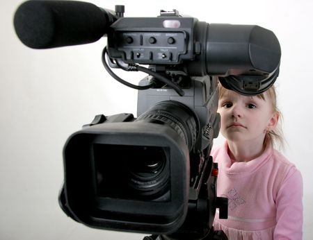 finder: the little girl in pink dress look to the finder of dv-camcorder Stock Photo
