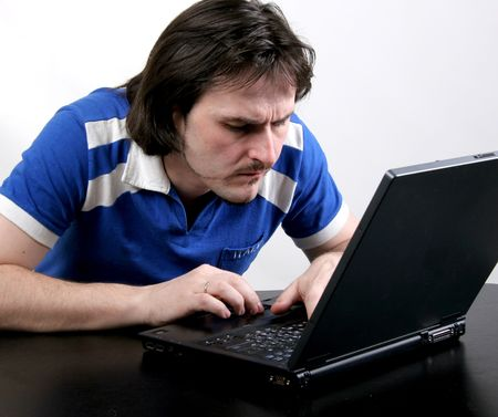 narrowly: man in blue t-shirt narrowly work with deep gray laptop