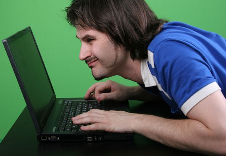 narrowly: man in blue t-shirt narrowly look to the display of deep gray laptop