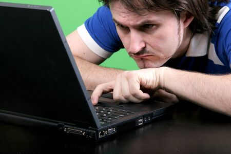narrowly: emotional man in blue t-shirt narrowly look to the display of deep gray laptop with green background