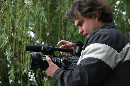 cameraman with dv-camcorder work on nature near the weeping willows photo