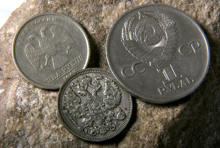 doubleheaded: silver russian coin with doubleheaded eagle, nickel USSR coin and modern russian coin lay at the grey stone Stock Photo