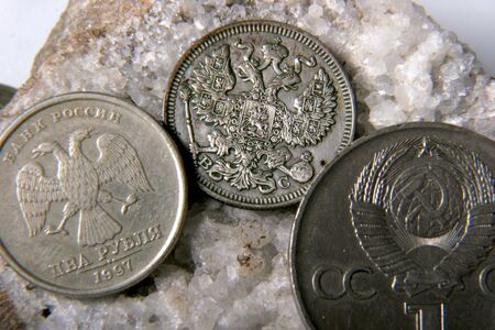 argentum: silver russian coin with doubleheaded eagle, nickel USSR coin and modern russian coin lay at the grey stone Stock Photo