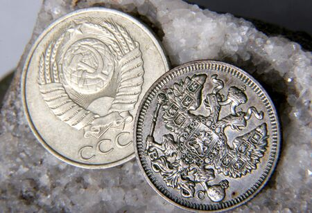 argentum: silver russian coin with doubleheaded eagle and nickel USSR coin lay at the grey stone
