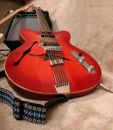 the red electric guitar lay on the amlifier near other guitar