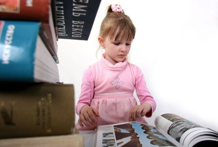 erudition: little girl in pink dress read the big book near the heap of bigger book Stock Photo