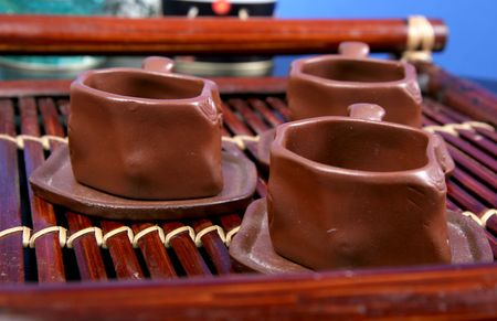 brown clay cups for tradition chinese and japanese tea ceremony stay on the bamboo tea-tray photo