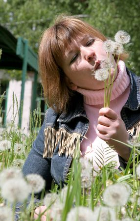 woman in the middle of dandelion field blow to someone dandelions Stock Photo - 3303811