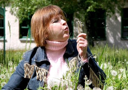 woman in the middle of dandelion field blow to someone dandelions Stock Photo - 3303818