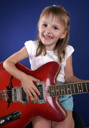 little girl playing with red electric guitar and singing Stock Photo - 3453284