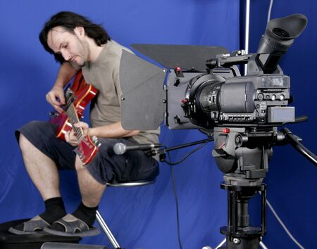 black high definition camcorder shot the guitarman in studio with blue background Stock Photo