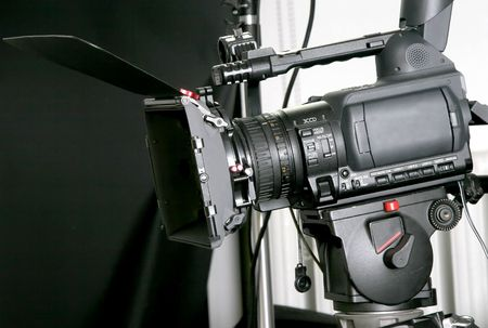 black high-definition camcorder with compendium on the tripod in studio