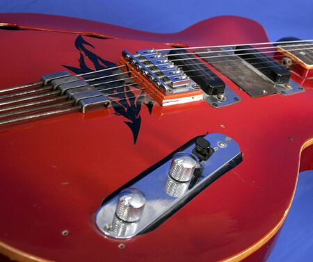 close-up part of red electric guitar with strings on blue background photo