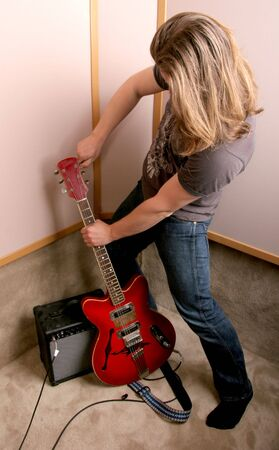 guitarist with red guitar make tuning in isolated audio studio photo