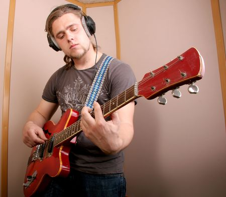 playing folk: guitarist with red guitar play music in audio studio