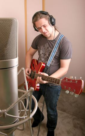 guitarist play in isolated studio with chrome microphone on crab support in front view photo