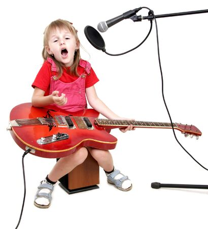 little girl sing to studio microphone and play with red electric guitar photo