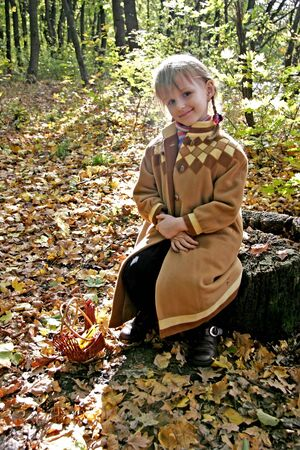 happy little girl sitting on the stumb in autumn forest photo