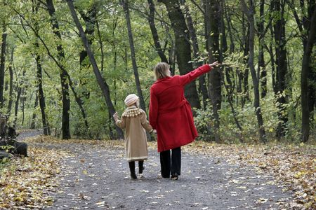 mother and the daughter walking by the autumn forest road photo