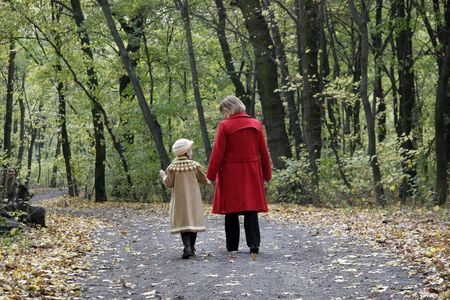 mother and the daughter walking by the autumn forest road