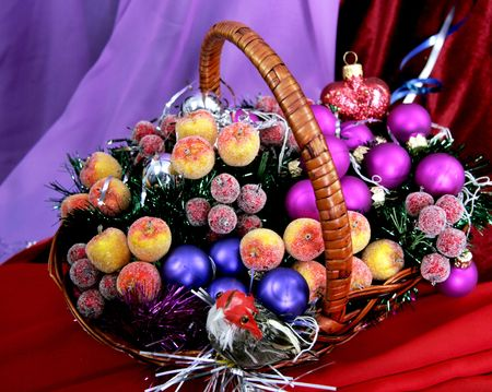decorative apples small purple balls and toy birdy on the wicker basket photo
