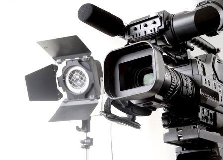 camara de cine: aislados c�mara de v�deo digital grabadora en tr�pode y luz de spot con fondo blanco